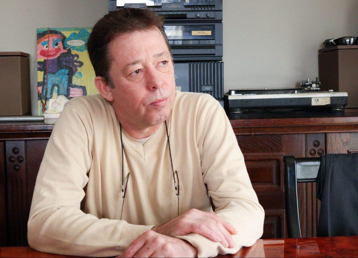 Johan Verschueren zit aan tafel in het huis van zijn moeder. Achter hem staat een muziekinstallatie.