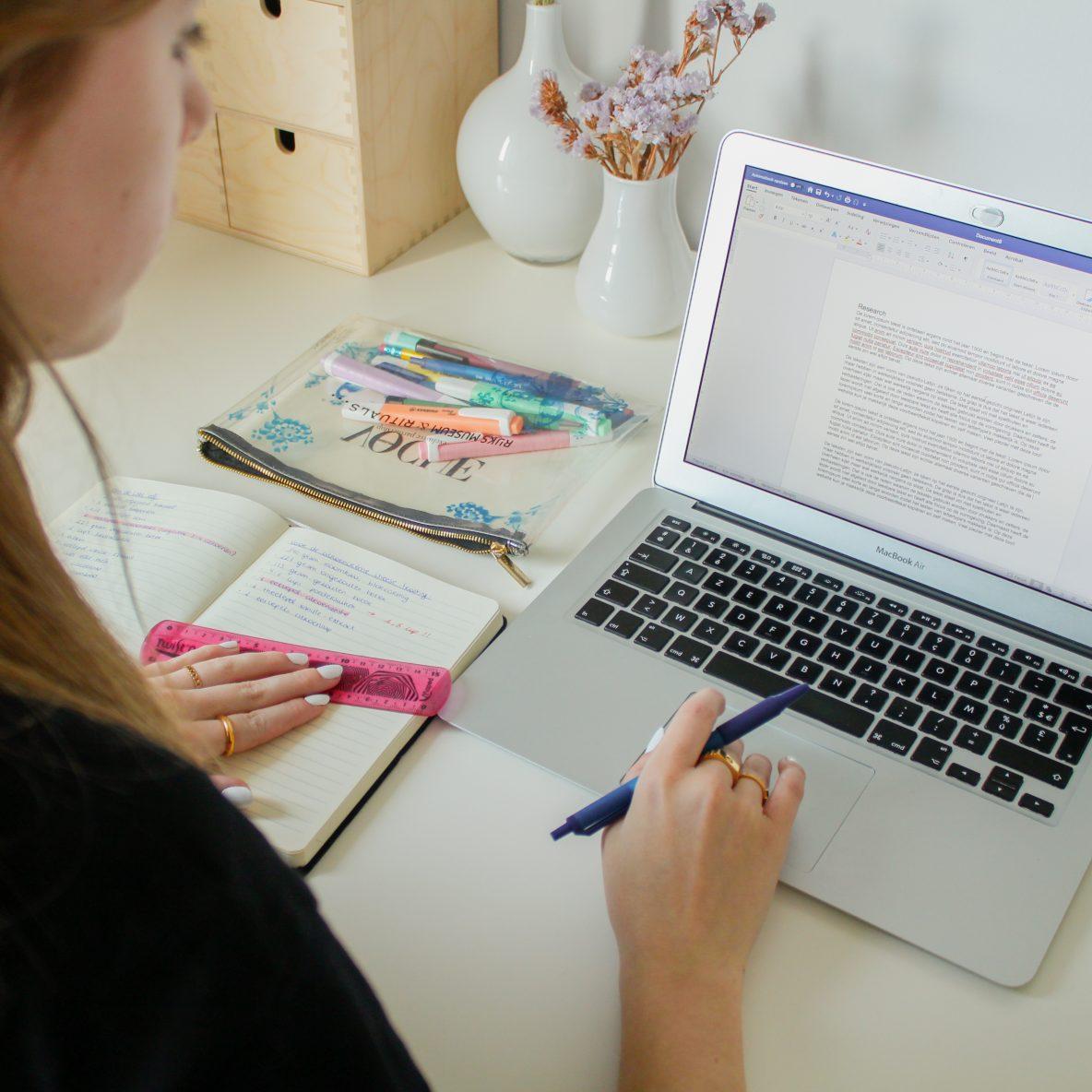 Persoon aan het werk van thuis uit aan een laptop